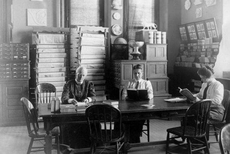 Fra venste: Dr. Agnes Mathilde Wergeland (med briller), Dr. Grace Hebard, tredjeperson er ukjent. Bildet er tatt i biblioteket på Universitetet i Wyoming.