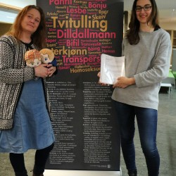 Hege Braathen and Dijana Stupar, two of those who initiated the auction bid, pose with the manuscript and to custom made doll versions of characters Isak and Even, also known under their couple name EVAK.